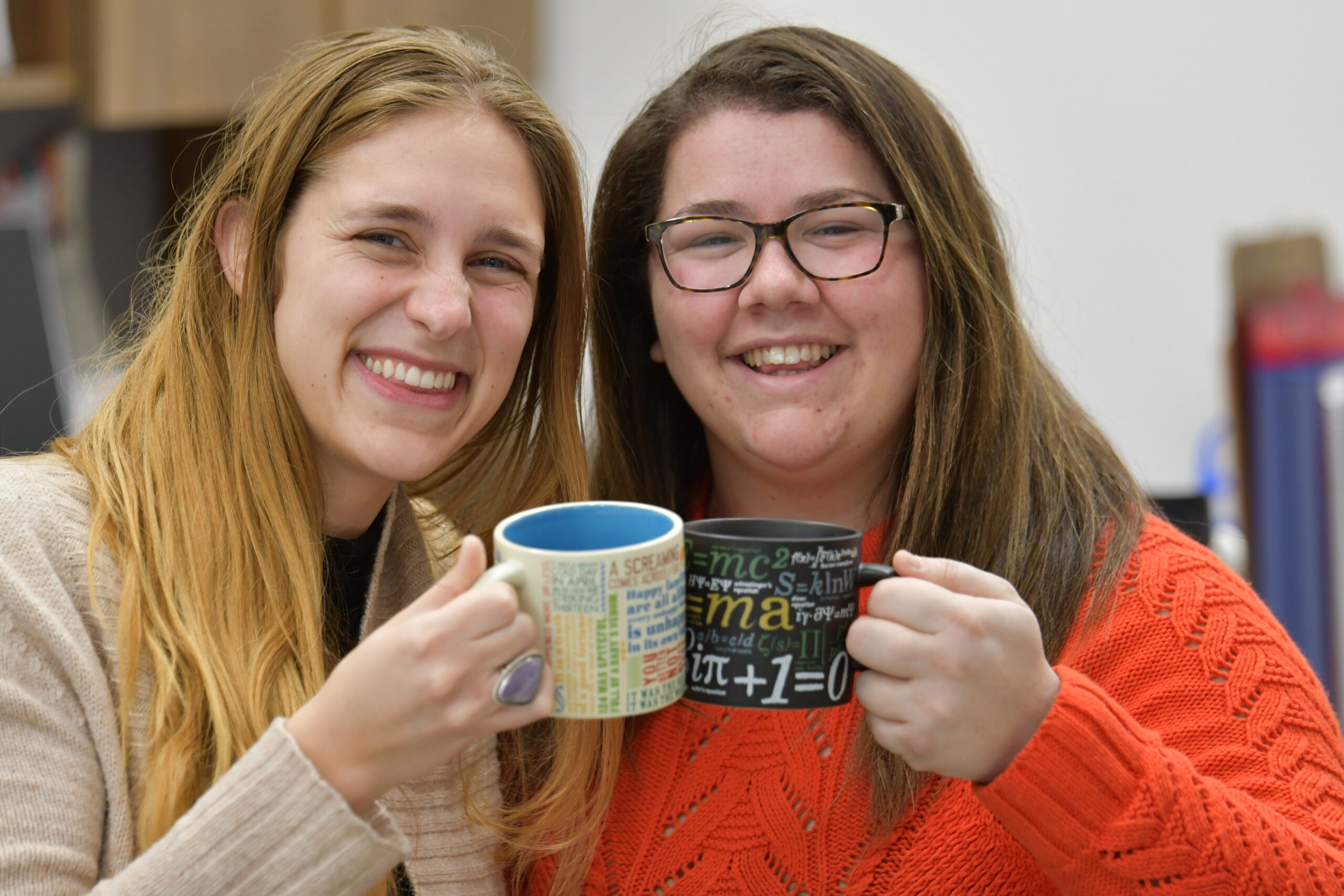 Two teachers hold mugs and smile at the camera