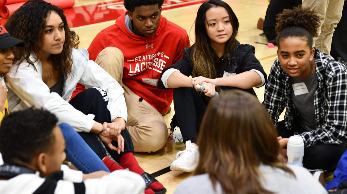 Students sit in a circle on the floor